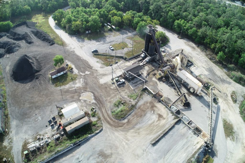 Aerial photo of asphalt plant and stockpiles with forest in background